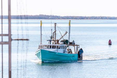New Bedford, Massachusetts, USA - May 14, 2020: Commercial fishing boat Underwing, hailing port Kingston, MA, nearing hurricane barrier