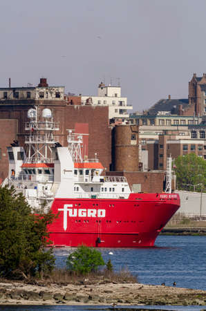 New Bedford, Massachusetts, USA - May 11, 2020: Research vessel Fugro Searcher framed against New Bedford skyline as she makes short trip to reposition herself