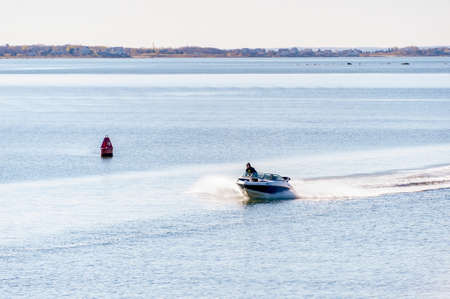 New Bedford, Massachusetts, USA - May 14, 2020: Speedboat crossing New Bedford outer harbor on chilly Spring morning Redactioneel