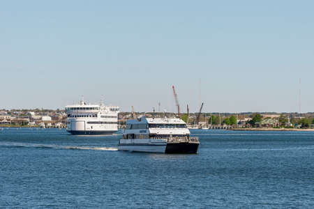 New Bedford, Massachusetts, USA - May 20, 2020: High-speed ferry Nantucket Express leaving New Bedford as vehicle ferry Island Home leaves Fairhaven