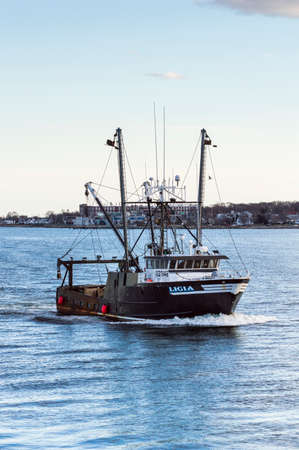 New Bedford, Massachusetts, USA - March 11, 2018: Commercial fishing vessel Ligia approaching New Bedford inner harbor on evening in late winter Editorial