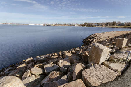 Wide-angle view of Fairhaven shoreline of New Bedford harbor with hurricane barrier in foreground