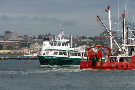 New Bedford, Massachusetts, USA - June 11, 2020: Ferry M/V Cuttyhunk and fishing boat William & Lauren passing Palmer Island lighthouse