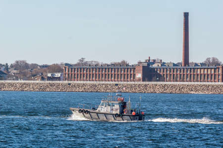 New Bedford, Massachusetts, USA - February 19, 2018: Pilot boat passing New Bedford factory on her way toward Buzzards Bay