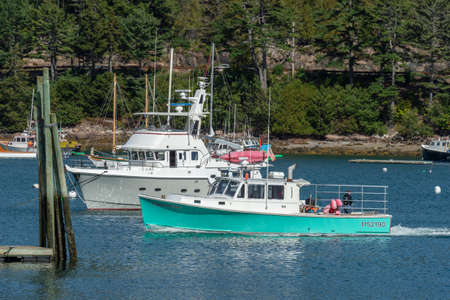 Northeast Harbor, Maine, USA - September 22, 2018: Lobster boat Emma Marie cruising past motor yacht in Northeast Harbor on last day of summer