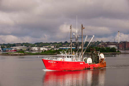 New Bedford, Massachusetts, USA - July 1, 2020: Commercial fishing boat Mary K glowing in sunlight that has found a hole in the clouds
