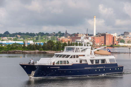 New Bedford, Massachusetts, USA - July 1, 2020: Luxury yacht Casual Water leaving New Bedford under storm clouds