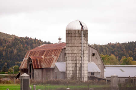 Family cemetery in foreground of old New Hampshire barn and silo