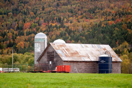 New Hampshire, USA - September 30, 2009: Barn and silos against mountainside with trees in fall colors