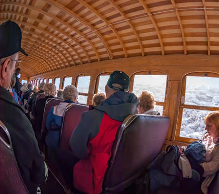 Mount Washington, New Hampshire, USA - October 2, 2009: Morning sun begins to brighten passenger car as Cog Railway train climbs above cloud layer