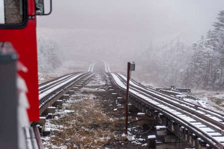 Mount Washington, New Hampshire, USA - October 2, 2009: Cog Railway train inches its way up the steep mountain after the first snowfall of the season