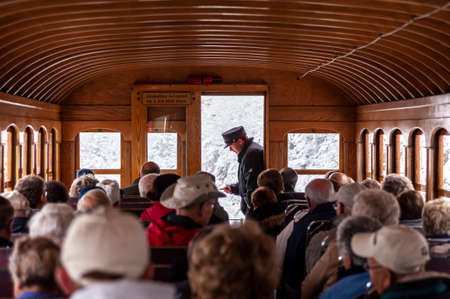 Mount Washington, New Hampshire, USA - October 2, 2009: Brakeman and passengers relax as Cog Railway train inches its way up the steep mountain