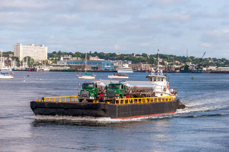 New Bedford, Massachusetts, USA - July 7, 2020: Tug Sirius pushing barge with fuel trucks aboard out of New Bedford