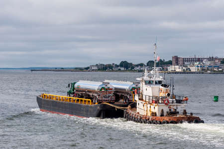 New Bedford, Massachusetts, USA - July 7, 2020: Tug Sirius pushing barge carrying fuel trucks out of New Bedford