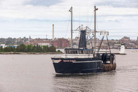 New Bedford, Massachusetts, USA - July 11, 2020: Commercial fishing boat Princess Scarlett, hailing port Cape May, New Jersey, passing lighthouse in New Bedford harbor