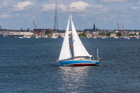 New Bedford, Massachusetts, USA - July 11, 2020: Sailboat tacking her way across New Bedford outer harbor toward Buzzards Bay on breezy summer morning
