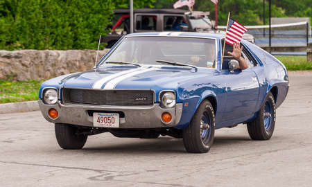 Fairhaven, Massachusetts, USA - July 4, 2020: AMC AMX muscle car passing Fort Phoenix during Fairhaven Fourth of July Car Cruise