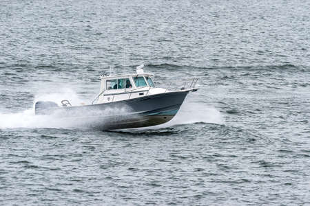 Fairhaven, Massachusetts, USA  - April 28, 2019: Powerboat hopping across choppy water in New Bedford outer harbor