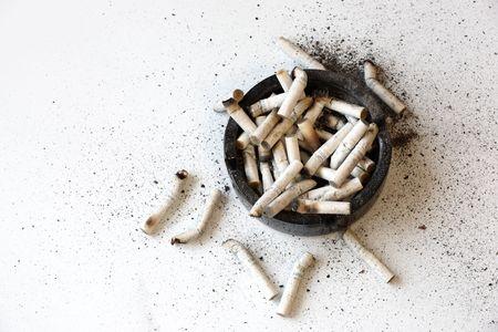 injurious: Cenicero completa de cigarrillos. Fumar es perjudicial para su salud.