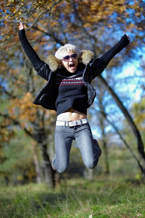 Beautiful Blonde jumping on the background of autumn nature photo