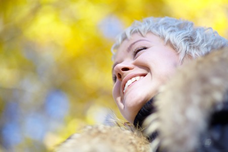 Smiling blond looks into the distance against the backdrop of yellow leaves photo