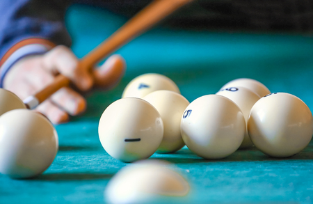 pool cue: The man playing billiard on snooker table