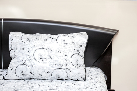 bedder: White pillow with black embroidered patterns on a powerful bed of ebony bedroom interior Stock Photo