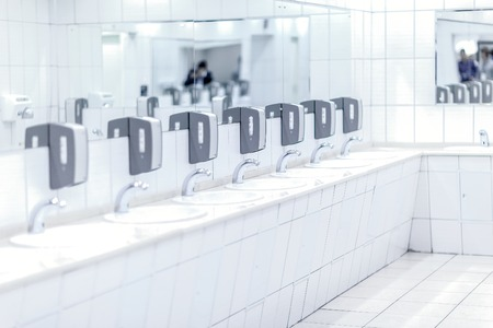 tiled: White shiny taps with gray soap holders and mirrors in  public toilet background in black   tone