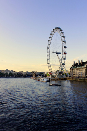 long shot: Long shot of London eye on Thames river in the evening Editorial