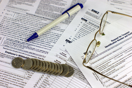 printout: Tax forms with glasses coins and pen