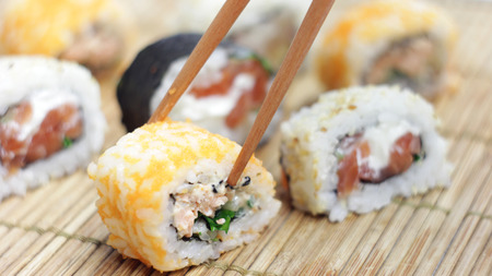 Eating sushi rolls with sticks.