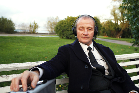Businessman with headphones enjoying music in the park.