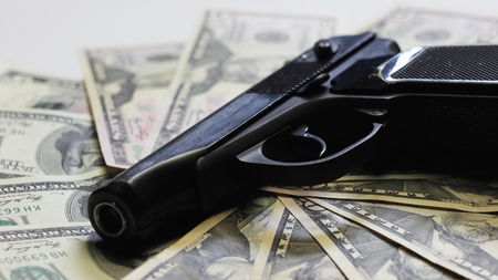 Gun and dollars as sign of organized crime. Stock Photo