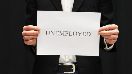 Businessman with unemployed sign on black background.