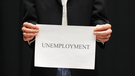 Businessman with unemployment sign on black background.