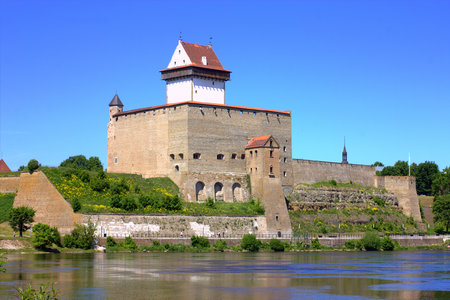 Narva city fortress on the bank of the river on a sunny summer day.
