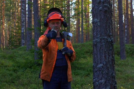 Lumberjack smiling into the camera and showing thumbs up middle shot.