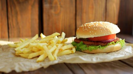 French Fries and Delicious Hamburger on Wooden Background