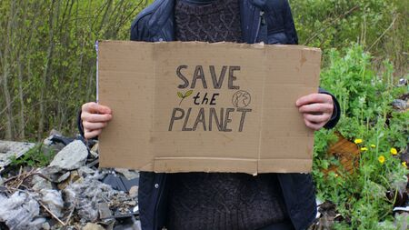 Man with Save the Planet Sign and Landfill in the Background 版權商用圖片
