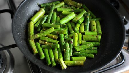 Fried Asparagus in a Pan. Restaurant kitchen photo.