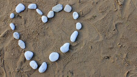 Heart Made with Pebbles on a Sunny Sea Shore