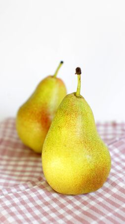 Two sweet ripe pears on kitchen napkin and white background still life 版權商用圖片