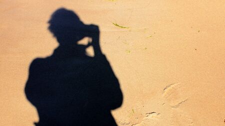 Silhouette of Man with Photo Camera Making a Photo of Himself on Sand