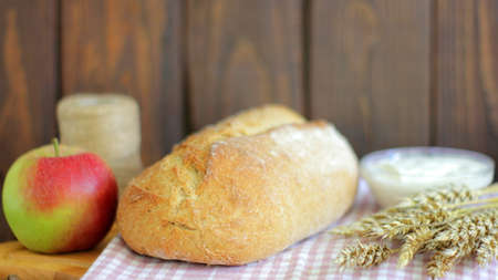 Seasonal Autumn Harvest with Bread and Wheat Ears as Products of Organic Farming.