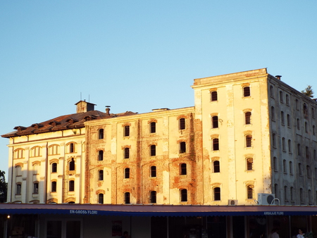 derelict: Boarded up derelict building facade peeling paint