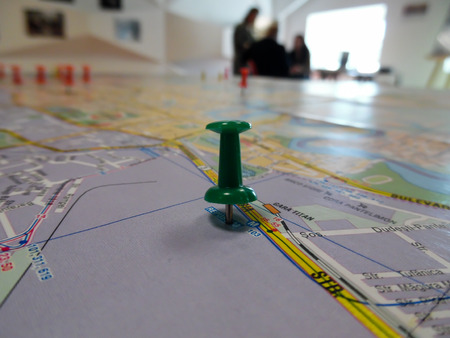 pinpoint: Pushpin marking a location on a road map