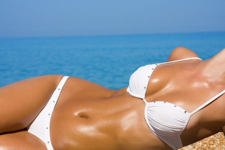 The sexual young blonde girl with a beautiful body sunbathes on a beach in a white bathing suit against the sea Stock Photo