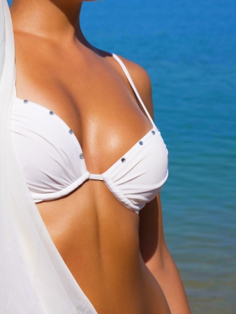The sexual young girl with a beautiful body sunbathes on a beach in a white bathing suit against the sea Stock Photo