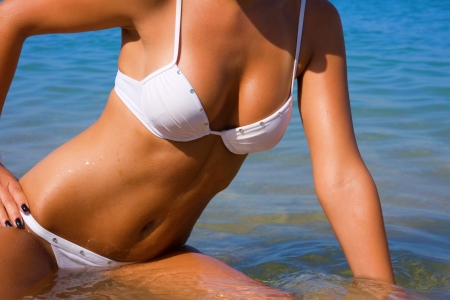The sexual young girl with a beautiful body sunbathes on a beach