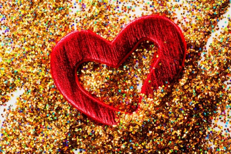 Red shiny heart against the background of tinsel
